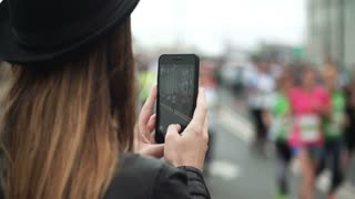 Back view of young woman using the smartphone to filming the video of big group of people running the marathon.
