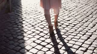 Back view of young woman walking in city centre in streets with paving stones. Stylish girl spending time alone.