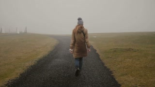 Back view of young woman walking through the field alone. Stylish female exploring the nature of Iceland.