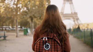 Back view of young woman walking with backpack near the Eiffel tower in Paris, France. Tourist enjoying the view.