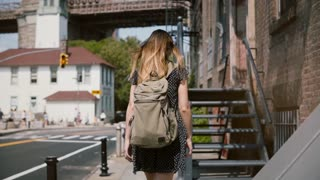 Back view of young woman with backpack and long hair walking up old metal stairs to enter red brick building slow motion
