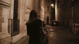 Back view of young woman with backpack walking through the deserted lane alone and thinking in the evening.