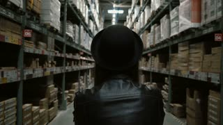 Back view of young woman with cart walking through the high shelves with goods for repair in big warehouse.