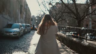 Back view of young woman with long hair walking in the city centre alone. Female going near the road and dreaming.