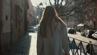 Back view of young woman with long hair walking in the street at bright sunny day. Female tourist exploring the new city