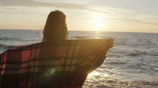 Back view of young woman with plaid enjoying the sunset on the windy beach with stretched arms. Freedom concept.