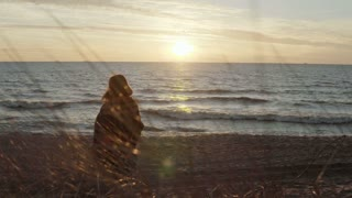 Back view of young woman with plaid on the shore of sea and looking into the distance. Pensive woman at beach on sunset.