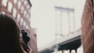 Back view professional female photographer with camera takes pictures of Brooklyn Bridge at Dumbo District, New York 4K.