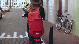 Back view. Student Caucasian girl rides a bicycle. Slow motion. Happy local daily commuter. Lifestyle background shot.