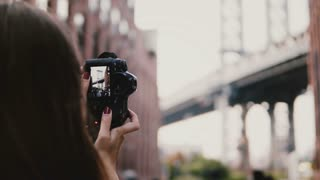 Back view unrecognizable woman with camera takes photos of Brooklyn Bridge at Dumbo District in New York City 4K.
