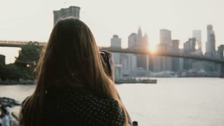 Back view woman with camera taking photos of amazing Brooklyn Bridge sunset cityscape panorama in New York City 4K.