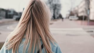 Back view woman with long blonde hair walking. Businesswoman in blue coat with beautiful long fair hair. Slow motion.