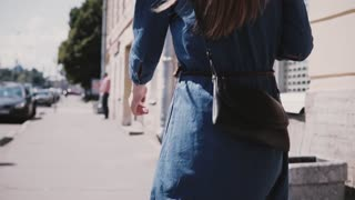 Back view young female fashion blogger in a blue dress with long hair and stylish bag walking along street slow motion.
