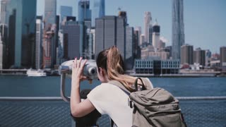 Back view young tourist girl looks through coin-operated binocular at city panorama of Manhattan, New York slow motion.
