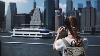 Back view young traveler girl looking through coin binoculars at epic panorama of Manhattan financial center, New York.