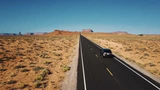Beautiful aerial shot of silver car driving along amazing American desert road towards mountains in Monument Valley.