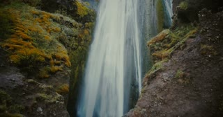 Beautiful aerial view of Gljufrabui waterfall in Iceland. Copter flying near the turbulent flow of water falling down.