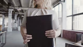 Beautiful blonde female manager walks through the office, controls the work at office, gives direction to colleague.