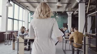 Beautiful blonde female team leader walk through the office, controls the work of employee, gives direction to colleague