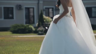 Beautiful bride walking outside before wedding ceremony. Woman stops and turns around in wedding dress. Slow motion.