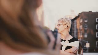 Beautiful calm Caucasian blonde girl with short hair in eyeglasses looking away at photoshoot outside, posing at camera.