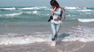 Beautiful Caucasian girl runs from waves on beach. Gorgeous woman smiles at camera. Wind blowing in hair. Slow motion.