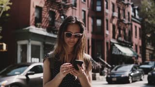 Beautiful Caucasian girl standing near famous old red brick New York City buildings, using smartphone app slow motion.