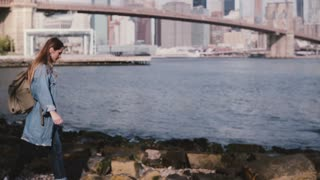 Beautiful Caucasian girl with backpack walking on stone river bank with coffee at amazing New York skyline slow motion