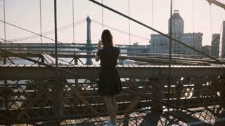 Beautiful Caucasian woman walks along Brooklyn Bridge, New York, stops and takes smartphone photo of scenic view 4K.