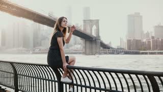 Beautiful Caucasian young woman sitting on river embankment fence at Brooklyn Bridge New York, jetski passing by 4K.