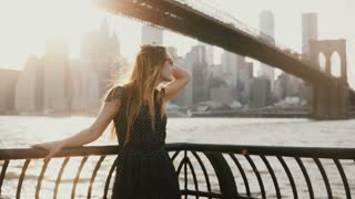 Beautiful Caucasian young woman with hair blowing in the wind posing for camera on amazing sunset river quay New York 4K