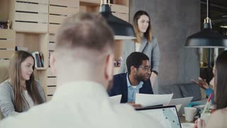 Beautiful European female business coach motivates office workers. Woman boss gives instructions to multiethnic team 4K.