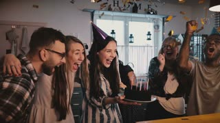 Beautiful European girl holds birthday cake, celebrates with happy multiethnic friends and amazing confetti slow motion.