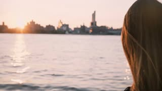 Beautiful European girl with long hair blowing in the wind stands by the water looking at New York city sunset 4K.