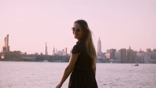 Beautiful European woman in sunglasses looks back at camera smiling, enjoying summer sunset, slow motion medium shot.