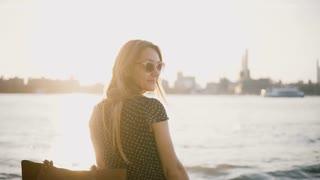 Beautiful European woman in sunglasses looks back at camera, turns away on sunny city beach. Enjoying summer sunset 4K.