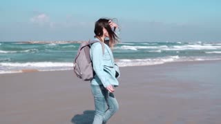 Beautiful European woman walks on sunny seashore. Pretty girl looks at camera smiling. Wind blowing in hair. Slow motion
