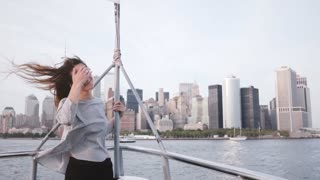 Beautiful excited traveler girl with flying hair and arms wide open watching New York skyline on a tour boat slow motion