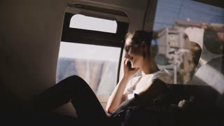 Beautiful happy Caucasian girl smiling, talking on phone and hanging up while traveling on modern train window seat.