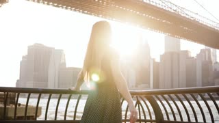 Beautiful happy Caucasian girl spinning on scenic sunset river embankment near Brooklyn Bridge, New York slow motion.