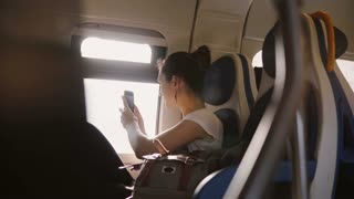 Beautiful happy Caucasian girl taking a smartphone photo from moving train window and posting it to a social network.