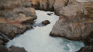 Beautiful landscape of the North nature. Turbulent stream of blue water in the mountains, flowing through the rocks.