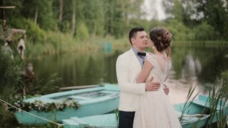 Beautiful lovers kiss near a pond with blue boats on it in a beautiful place. Bride and groom enjoy their wedding day