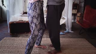 Beautiful multiethnic couple in pajamas dancing together and smiling. Man and woman having fun. Slow motion.