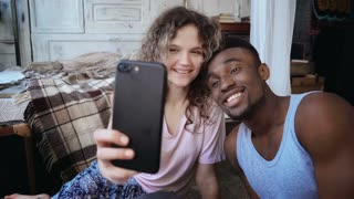 Beautiful multiethnic couple take the selfie photo on smartphone. Woman hold the smartphone, man kisses her and laughs.