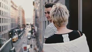 Beautiful multiethnic romantic couple walking down metallic New York City stairs holding hands, amazing street panorama.