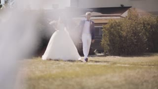 Beautiful newlyweds walking outside in nature. Groom kisses his bride, happy man and woman in wedding day.