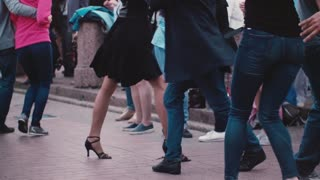Beautiful slow motion shot of many people dancing together and having fun at a Latin American festival in the street.