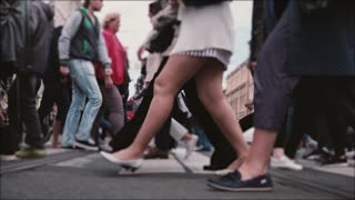 Beautiful slow motion shot of people's legs and feet walking across a busy old city street with tram rails in the middle