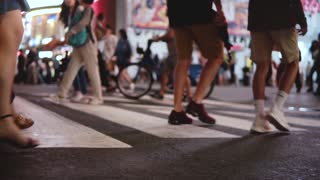 Beautiful slow motion shot of young female freelancer crossing a busy crowded street at night in Times Square, New York.